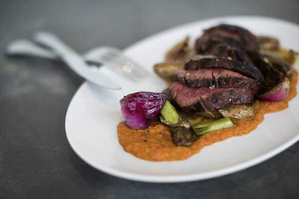 Wood-grilled hanger steak with Spanish romesco sauce, spring onions and fingerling potatoes at Indianola