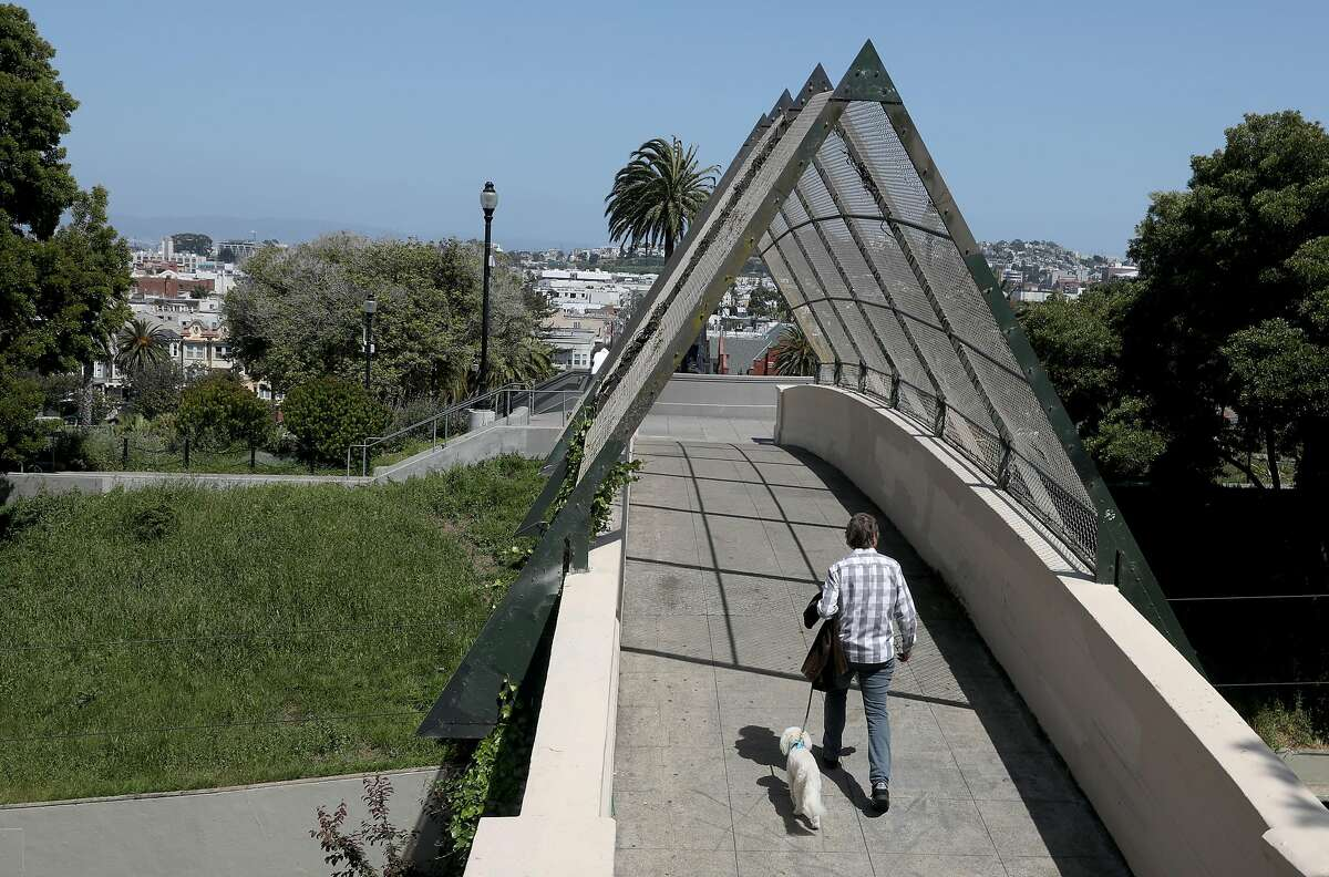 Hans Kolbe walks his dog, Kirby, on the bridge from 19th at Church streets leading to Dolores Park on Monday, April 29, 2019, in San Francisco, Calif.