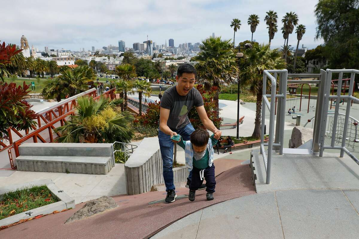 Daniel May climbs to the top of a slide with his nephew Nathan May at Dolores Park in San Francisco, California, on Monday, May 13, 2019. Community residents have propsed to tax themselves to fund extra street cleaning services for the park to keep it maintained.