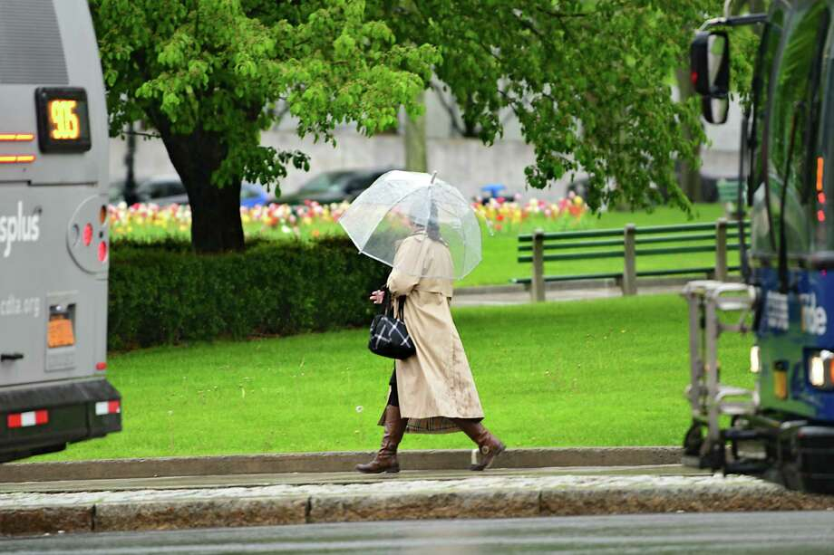 An umbrella might come in handy Thursday afternoon when forecasters say scattered but potentially strong thunderstorms could hit the Capital Region. In this photograph, a women uses an umbrella as she walks in front of the Capitol during a steady rain on Monday, May 13, 2019 in Albany, N.Y. (Lori Van Buren/Times Union) Photo: Lori Van Buren, Albany Times Union