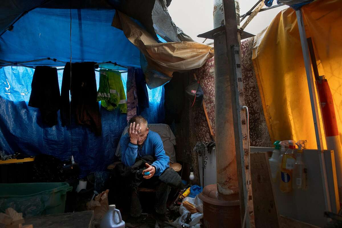 William Ewing, 55, an unemployed water tanker driver, in his makeshift tent he lives with his girlfriend on Thursday, Dec. 20, 2018, in Oakland, Calif. He said he's been homeless for 5-years.