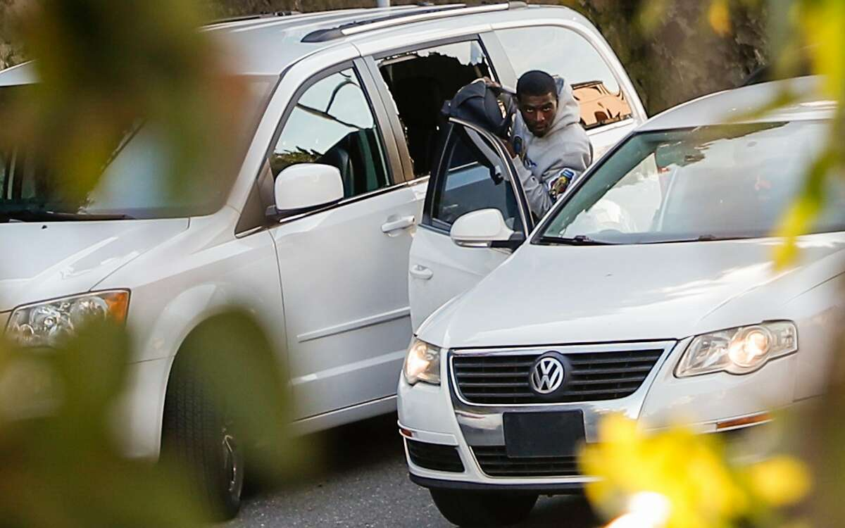 A man takes a bag through a broken window of a van parked on Lombard St. on Tuesday, Jan. 30, 2018 in San Francisco, Calif.