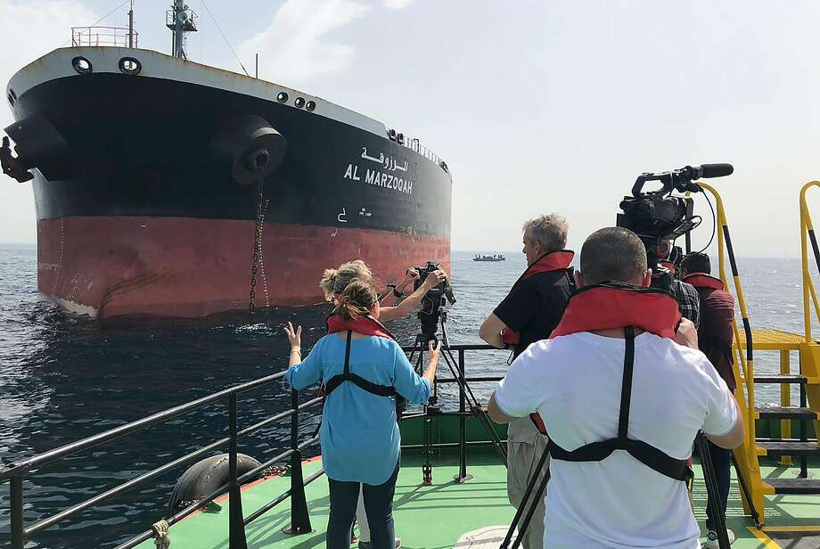 """A picture taken on May 13, 2019 off the coast of the Gulf emirate of Fujairah shows reporters taking images of the Saudi oil tanker Al-Marzoqah, one of the four tankers damaged in alleged """"sabotage attacks"""" in the Gulf the previous day. - Saudi Arabia said two of its oil tankers were damaged in mysterious """"sabotage attacks"""" in the Gulf as tensions soared in a region already shaken by a standoff between the United States and Iran. Photo: Handout, AFP/Getty Images"""