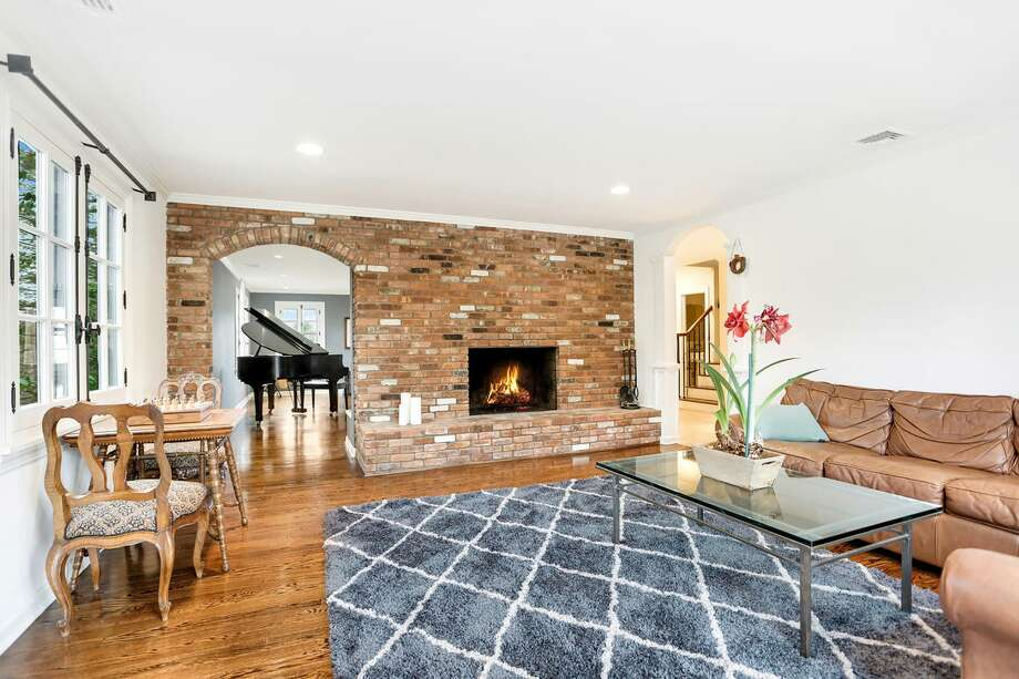 The family room features exposed brick, French doors and a wood-burning fireplace. The custom-designed five-bedroom is listed for $1.599 million. Photo: William Pitt Sotheby's International Realty / ONLINE_CHECK