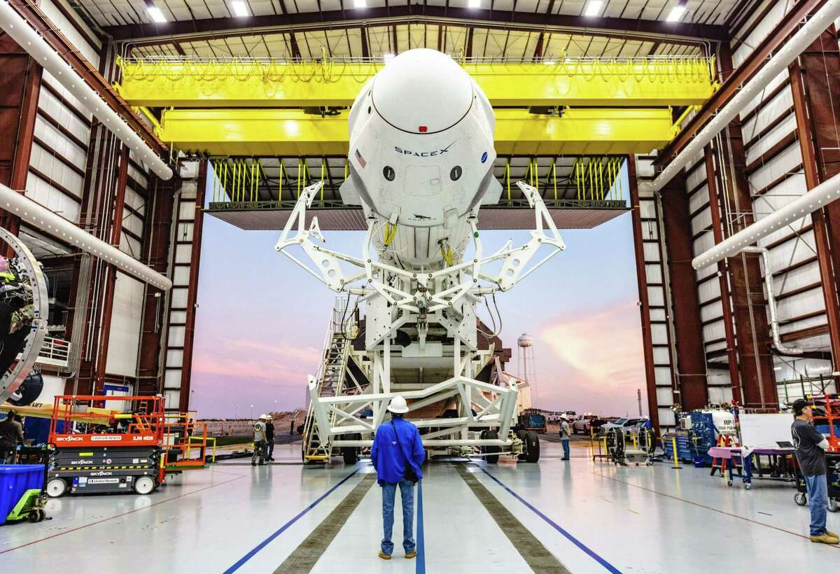 This photo obtained from NASA shows the SpaceX Falcon 9 rocket with the company's Crew Dragon attached, rolling out of the company's hangar at NASA Kennedy Space on Jan. 3, 2019.