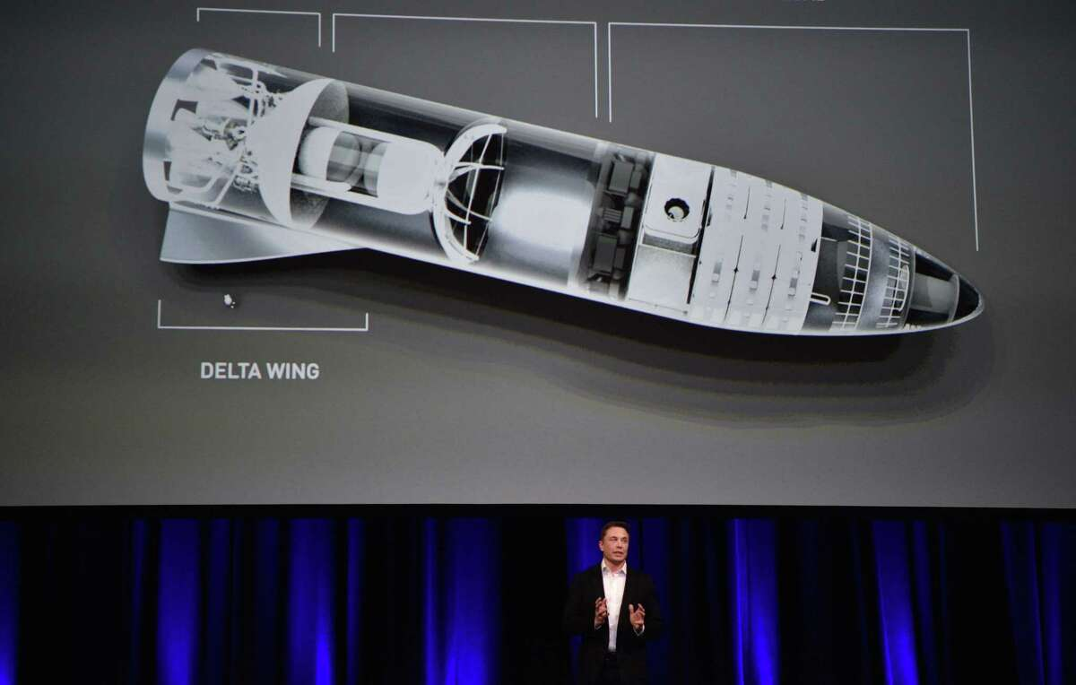 In this photo taken on Sept. 29, 2017, billionaire entrepreneur and founder of SpaceX Elon Musk speaks below a computer-generated illustration of his new rocket at the 68th International Astronautical Congress in Adelaide.
