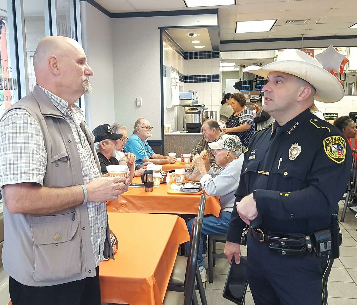 Bexar County Sheriff Javier Salazar speaks with Dr, George Patrin, left, on Saturday before addressing a standing-room-only crowd at the FM 78 Whataburger during one of the