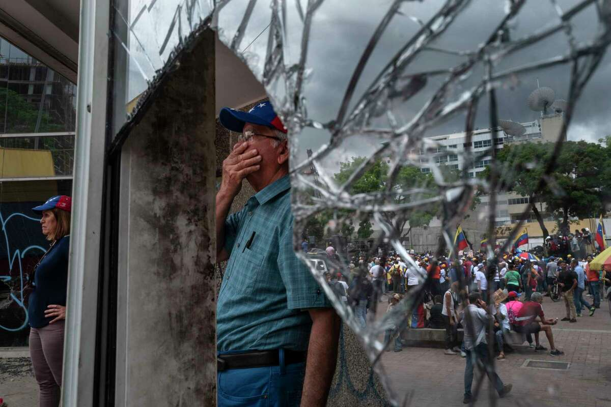 A man stands near a window shattered during protests in Caracas, Venezuela, on May 11, 2019.