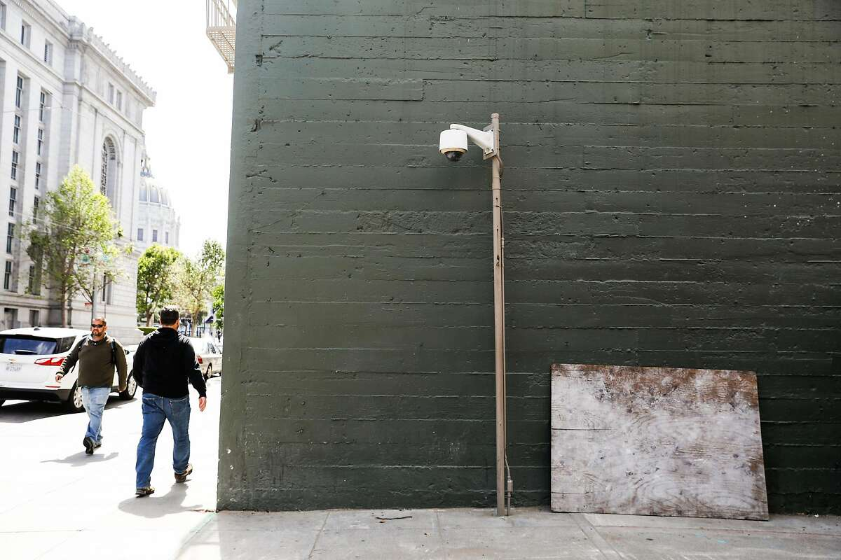 People pass by a security camera on McAllister Street in San Francisco, California, on Monday, May 13, 2019. The Board of Supervisors is considering a proposal to ban city departments from using facial recognition software. While privacy advocates applaud the move, others say it will keep the city from a useful tool in crime solving. San Francisco law enforcement agencies such as the police department and District Attorney's office, say they do not use facial recognition software.