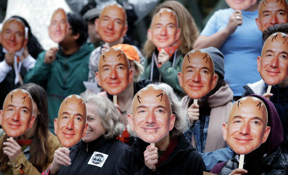 """FILE - In this Oct. 31, 2018, file photo, demonstrators hold images of Amazon CEO Jeff Bezos near their faces during a Halloween-themed protest at Amazon headquarters over the company's facial recognition system, """"Rekognition,"""" in Seattle. San Francisco is on track to become the first U.S. city to ban the use of facial recognition by police and other city agencies as the technology creeps increasingly into daily life. Studies have shown error rates in facial-analysis systems built by Amazon, IBM and Microsoft were far higher for darker-skinned women than lighter-skinned men. (AP Photo/Elaine Thompson, File) Photo: Elaine Thompson / Copyright 2019 The Associated Press. All rights reserved."""