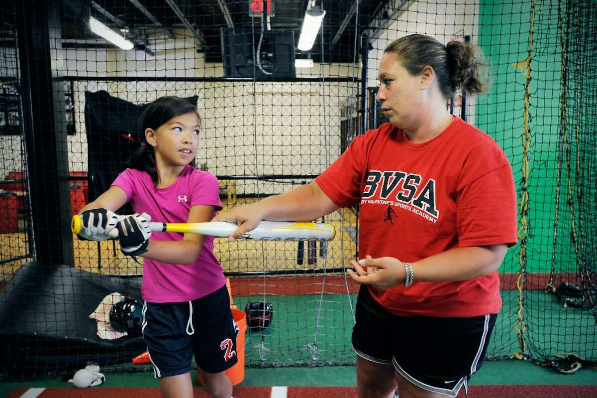 Danielle Simoneau works with softball player Sara Staley, 11 of Stamford, at Bobby Valentine's Sports Academy in Stamford, Conn. on Wednesday June 28, 2010. Simoneau is the new softball coach for New Canaan High School.