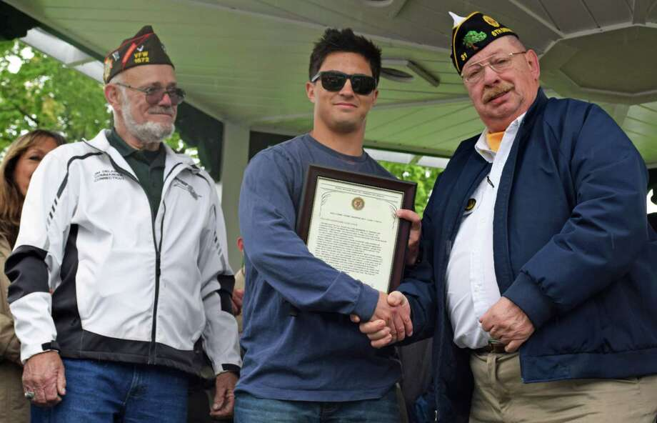 Spectrum/New Milford Marine Sgt. Liam Lynch received a surprise welcome home reception May 12, 2019 at the bandstand. Above, Ezra Woods Post 31 American Legion Commander Jeffrey McBreairty, right, presents a special welcome home certificate from the American Legion to Lynch, as Jim Delancy of the Andrew B. Mygatt Post 1672 VFW, and state commander of the VFW looks on. Photo: Deborah Rose / Hearst Connecticut Media / The News-Times  / Spectrum