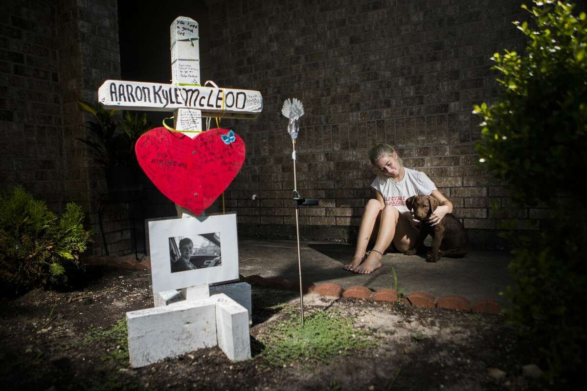 Danika McLeod sits with her emotional support dog by the memorial of her brother Aaron Kyle McLeod, Monday, Aug. 20, 2018, at her home in Santa Fe. McLeod was killed during the Santa Fe High School shooting.