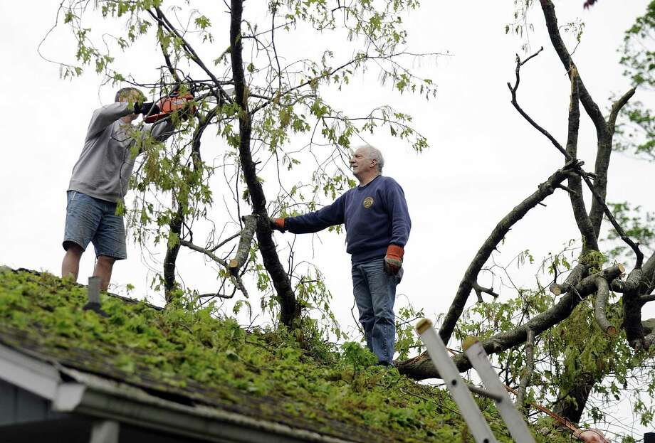 Keith W. Confalone, right, is helping to cut down branches from a roof on Skyline Drive in Brookfield where he is clearing fallen tree branches, Wednesday, may 16, 2018. Photo: Carol Kaliff / Hearst Connecticut Media / The News-Times