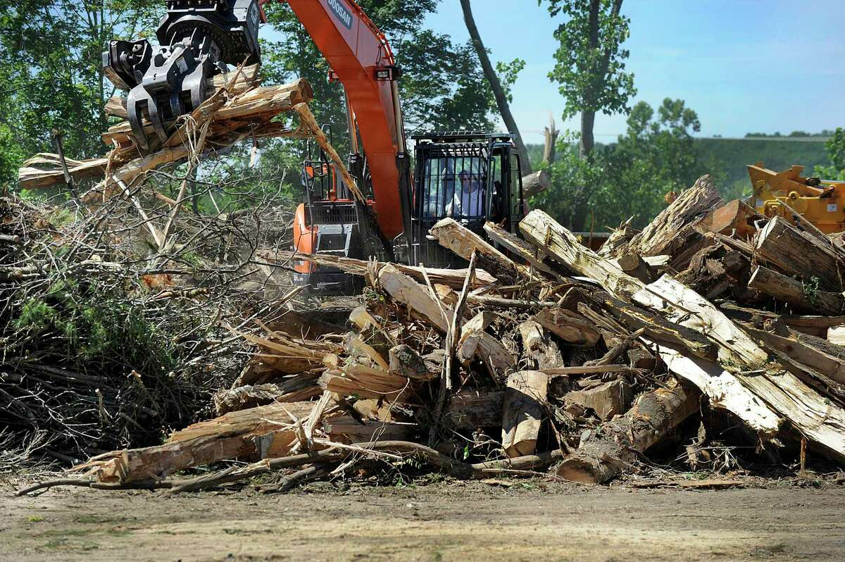 File photo of debris from the May 2018 macroburst is being processed at a brush yard behind the the Brookfield fire department near town hall. The trucks will be followed by FEMA officials who are monitoring the work to ensure it meets regulations.