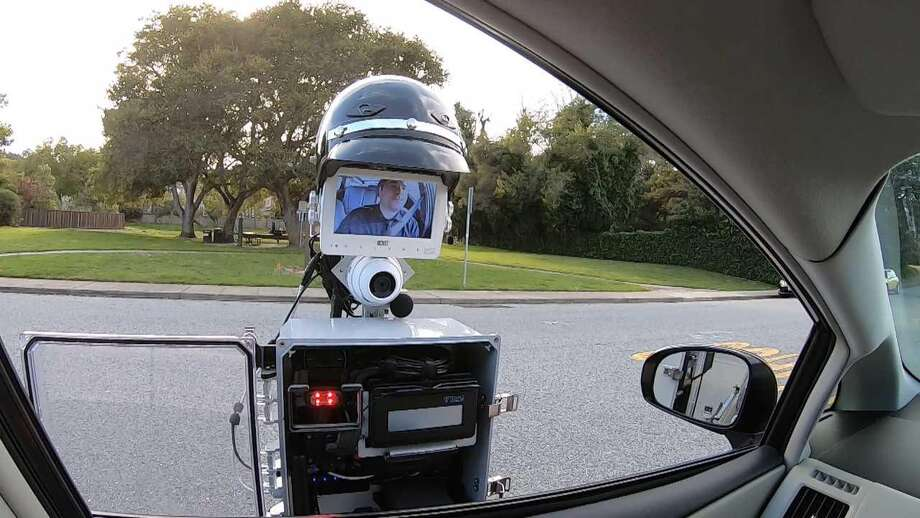 The GoBetween robot extends out from the police vehicle to the car that has been pulled over. When the encounter is done, the entire contraption retracts and the robot returns to the police car. Photo: Handout Photo Courtesy Of SRI International / Handout