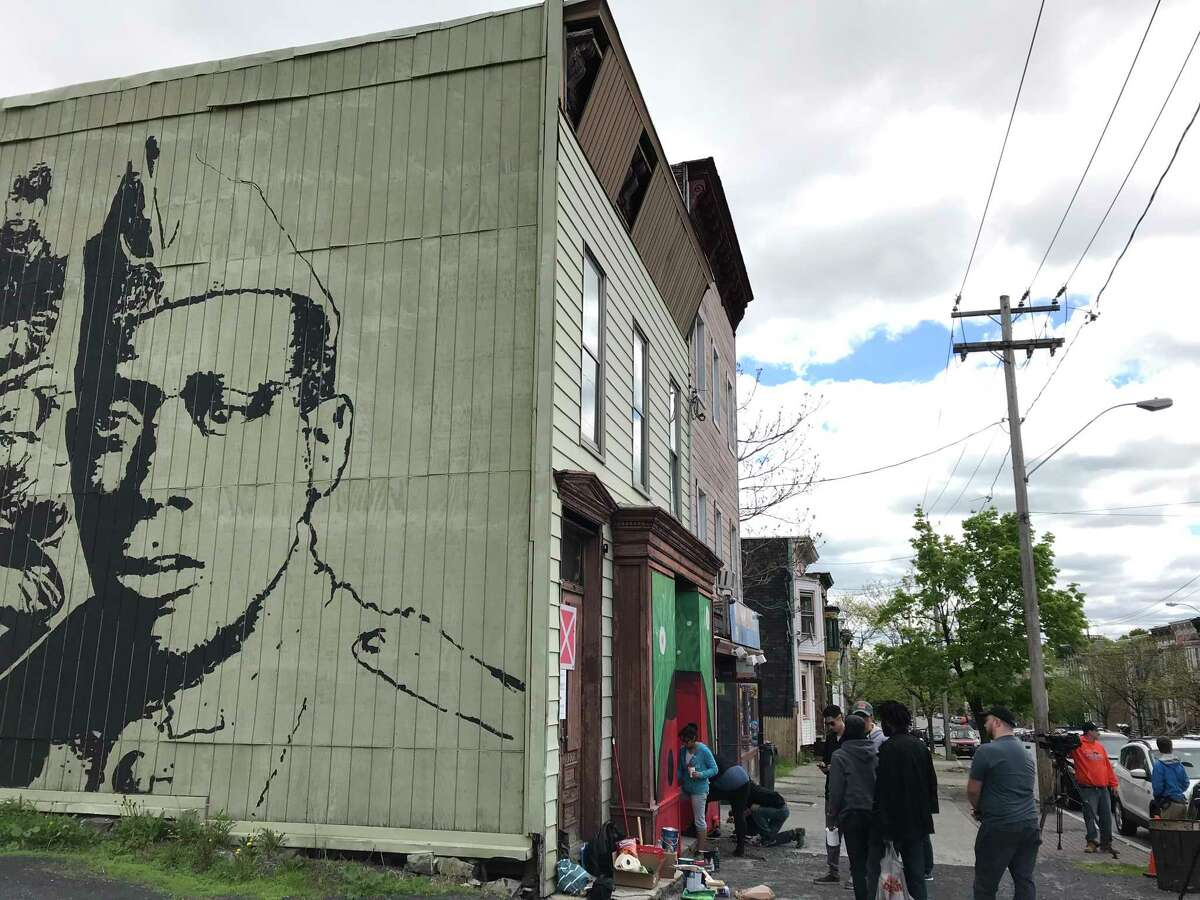 Students work on a Corner Canvas ladybug mural at 337 Clinton Ave.; on the abutting wall is Samson Contompasis' 2018 mural of WWI hero Henry Johnson (photo by Amy Biancolli)