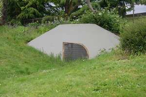 WSDOT's caption: Just north of the main entrance to the fallout shelter is what appears to be a gated-off culvert. In actuality, it's the exit to the emergency tunnel.