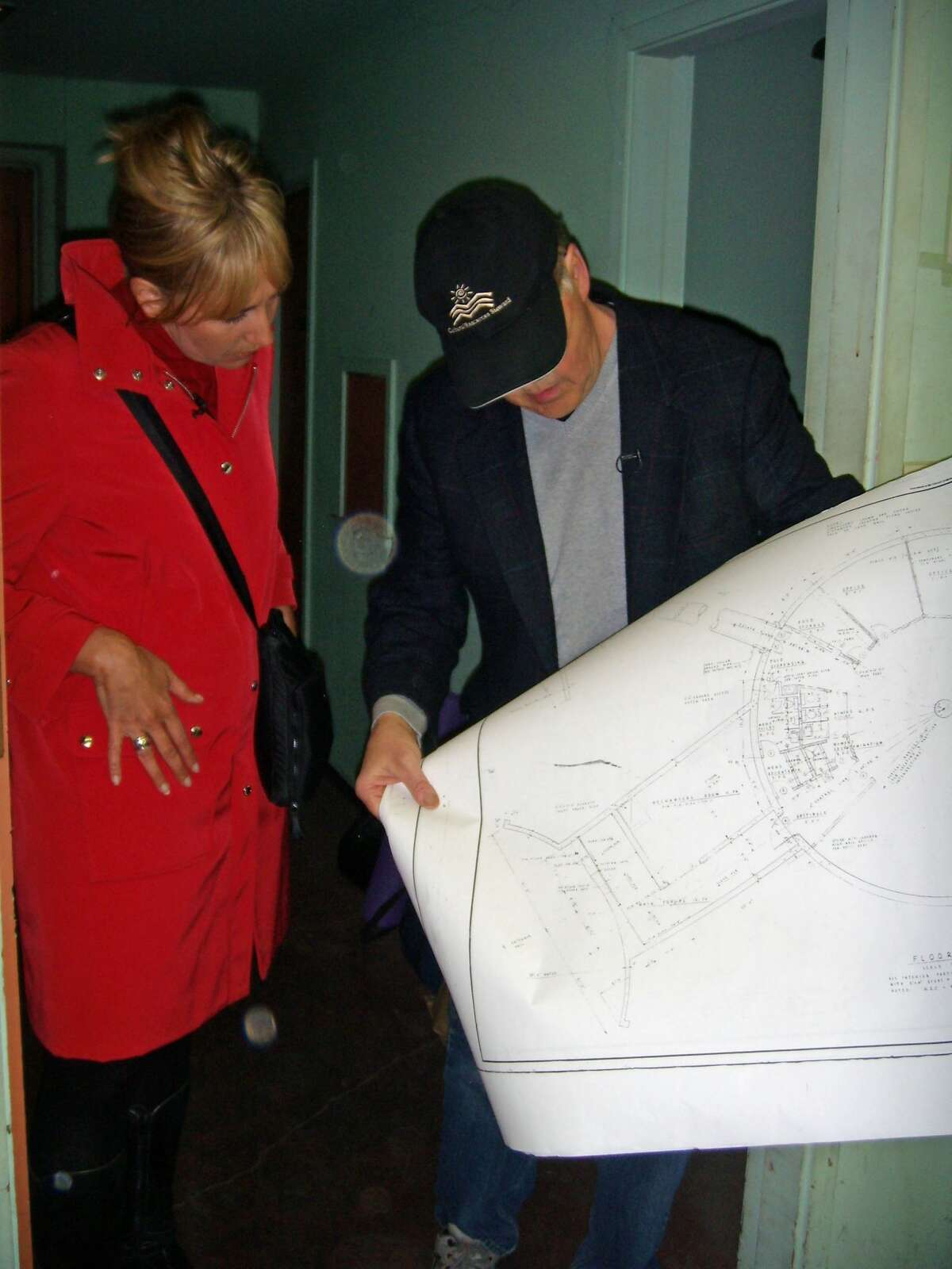 WSDOT's caption:KOMO reporter Michelle Esteban and WSDOT historian Craig Holstine look at the original plans for the fallout shelter.