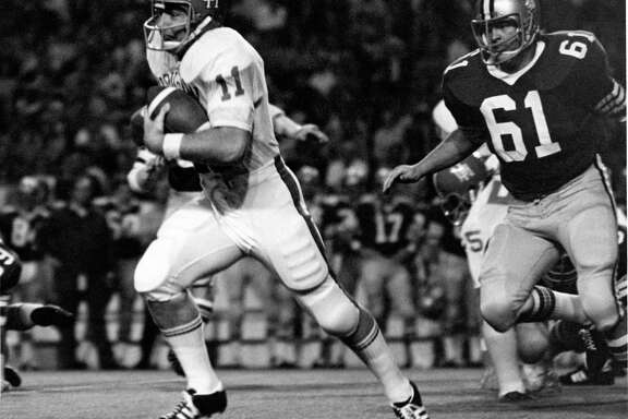 University of Houston quarterback Gary Mullins (11) zips past Rice's Randy Alford (61) for a 17-yard gain during the 1971 footbal season. Mullins is retiring as a coach at the end of this school year.