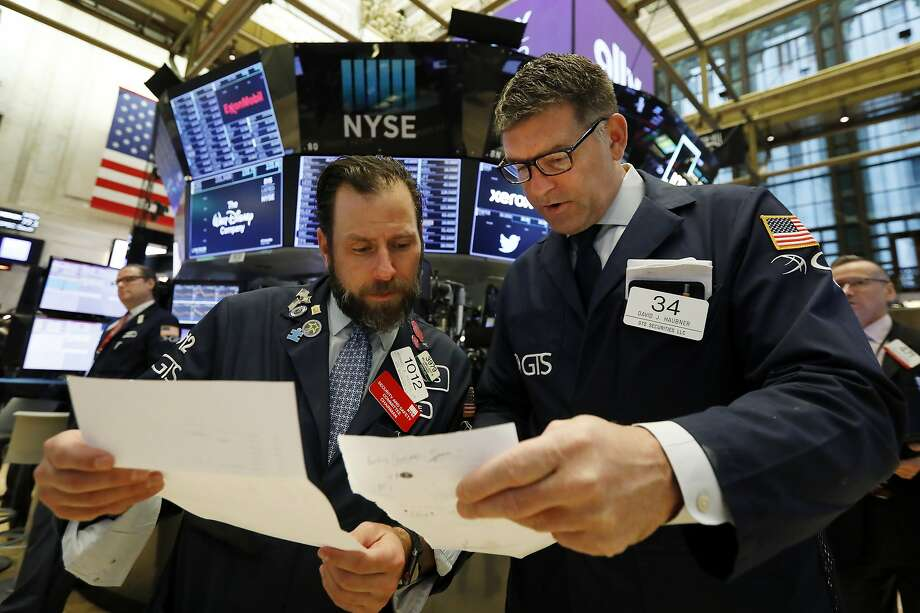 Specialists Michael Pistillo (left) and David Haubner confer on the floor of the New York Stock Exchange, as stocks recovered after Monday's big plunge. Photo: Richard Drew / Associated Press