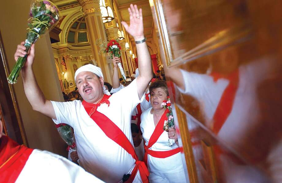 Nick Fazzino of Middletown, left, shouts with other I Nuri runners as they leave St. Sebastian Church during the 83rd anniversary of the feast. This year's festival, the 98th annual, runs Friday night through Sunday at 155 Washington St. Photo: File Photo