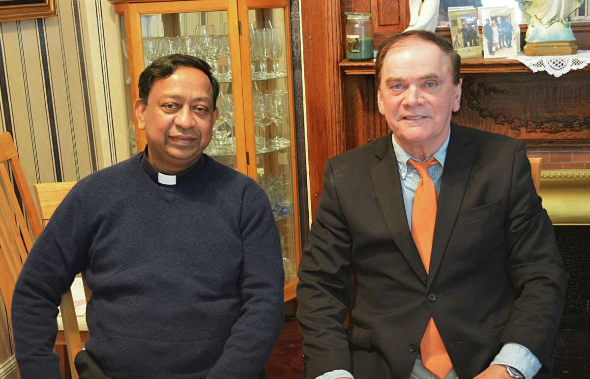 The Rev. James Thaikoottathil, left, and Middletown Common Councilman and feast general chairman Eugene Nocera, right, explain what fair goers can expect this weekend at the 98th annual St. Sebastian Church feast at the church, 155 Washington St.