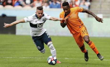Vancouver Whitecaps midfielder Lucas Venuto (7) grabs the jersey of Houston Dynamo forward Romell Quioto (31) as the go after the ball during the second half of a Major League Soccer match at BBVA Compass Stadium on Saturday, March 16, 2019, in Houston.