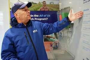 The National Institutes of Health's All of Us Journey, a traveling, hands-on exhibit to raise awareness about the All of Us Research Program, was parked near the Community Health Center on Main Street Tuesday. Here, tour manager Steve Curran asks participants questions related to lifestyle, genetics and environment. Depending on their response, he turns a dial which corresponds with colored pebbles that fall into a container to reveal a unique profile.