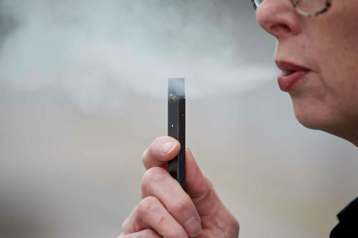 FILE - In this April 16, 2019, file photo, a woman exhales a puff of vapor from a Juul pen in Vancouver, Wash. (AP Photo/Craig Mitchelldyer, File)