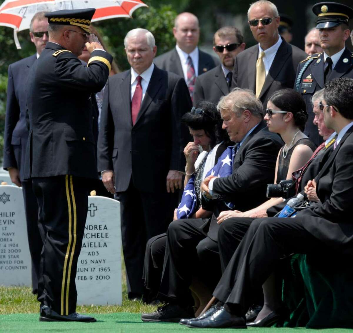 Defense Secretary Robert Gates, center, watches as Maj. Gen. Richard Formica, left, salutes greets Leslie Miller, seated left, and Jesse Miller, seated second from left, parents of Army Pfc. David Taylor Miller, during his funeral service at Arlington National Cemetery in Arlington, Va., Wednesday, July 28, 2010. Miller of Wilton died June 21 in Afghanistan. (AP Photo/Susan Walsh)