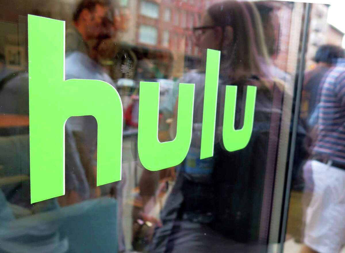 FILE - This June 27, 2015, file photo, shows the Hulu logo on a window at the Milk Studios space in New York. Disney has struck a deal with Comcast that gives it full control of streaming service Hulu. The companies said Tuesday, May 14, 2019, that as early as January 2024 Comcast can require Disney to buy NBCUniversal?s 33% interest in Hulu and Disney can require NBCUniversal to sell that stake to Disney for its fair market value at that future time. (AP Photo/Dan Goodman, File)