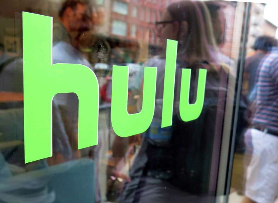 FILE - This June 27, 2015, file photo, shows the Hulu logo on a window at the Milk Studios space in New York. Disney has struck a deal with Comcast that gives it full control of streaming service Hulu. The companies said Tuesday, May 14, 2019, that as early as January 2024 Comcast can require Disney to buy NBCUniversal?s 33% interest in Hulu and Disney can require NBCUniversal to sell that stake to Disney for its fair market value at that future time. (AP Photo/Dan Goodman, File) Photo: Dan Goodman / Copyright 2016 The Associated Press. All rights reserved. This m