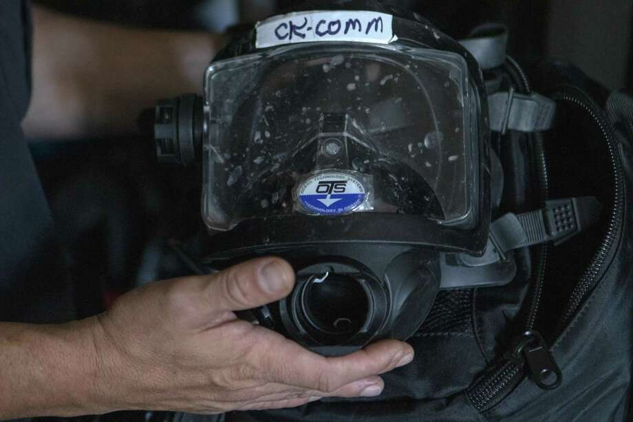 Lt. Tim Cade, with the Montgomery County Precinct One Constable's Office Lake Patrol Division, explains the communication system in the masks divers use to keep in contact with each other and the surface Tuesday inside a mobile dive unit in Conroe. Photo: Cody Bahn, Houston Chronicle / Staff Photographer / © 2018 Houston Chronicle