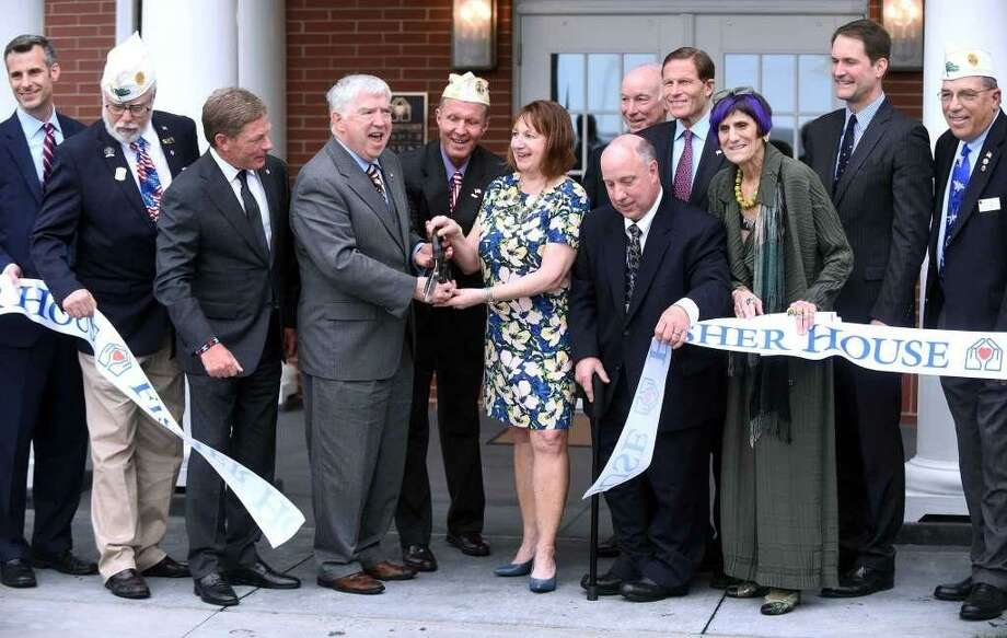 Second from left, holding scissors, Kevin Creed, volunteer CEO, director and founder of the Friends of Fisher House Connecticut, cuts the ribbon during a dedication ceremony at Fisher House. Creed, an attorney, is accused of embezzling from the Friends' fundraising account. Photo: File Photo By Arnold Gold / Hearst Connecticut Media