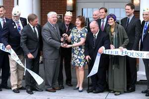Second from left, holding scissors, Kevin Creed, volunteer CEO, director and founder of the Friends of Fisher House Connecticut, cuts the ribbon during a dedication ceremony at Fisher House. Creed, an attorney, is accused of embezzling from the Friends' fundraising account.