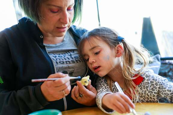 (l-r) Tink Moss and her daughter Genevieve Moss, 3, paint pottery at Terra Mia in Noe Valley in San Francisco, California, on Tuesday, April 30, 2019.