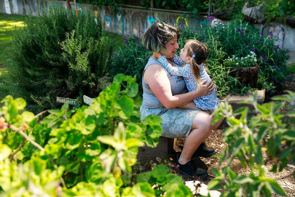 (l-r) Tink Moss and her daughter Genevieve Moss, 3, play in the garden outside her cooperative school in San Francisco, California, on Tuesday, April 30, 2019.
