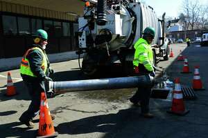 Heavy equipment operator Fred Davila and laborer Ramone Acevedo of the Norwalk Department of Public Works vacuum out a storm water catch basin on South Smith Street last month. Public Works is planning to address issues in flood-prone areas through maintenance of waterways and watercourses.