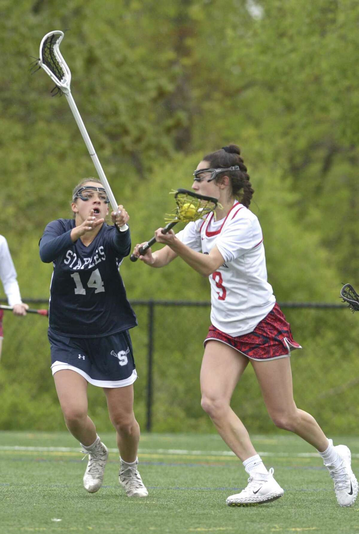 New Fairfield's Katelyn Sousa (9) moves to the goal while being defended by Staples Julia DiConza (14) in the girls lacrosse game between Staples and New Fairfield high schools, Tuesday May 14, 2019, at New Fairfield High School, New Fairfield, Conn.