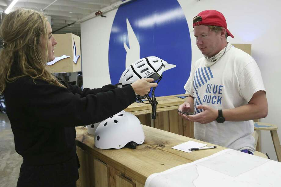 Chief Marketing Officer Elizabeth Houston shows CEO Eric Bell a collapsible helmet at the company's offices near the Pearl. Bell wants to position Blue Duck as the stylish but safety-conscious Volvo of scooter companies. Photo: Jerry Lara / © 2019 San Antonio Express-News