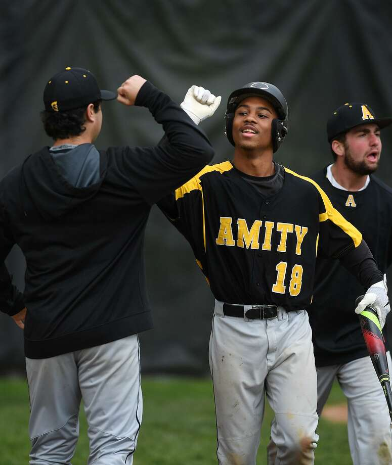 Amity's Julian Stevens high fives a teammate after scoring a run in the 4th inning against Hand on Tuesday in Madison. Photo: Brian A. Pounds / Hearst Connecticut Media / Connecticut Post