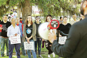 Faisan Syed, right, uses a bullhorn to talk to the crowd who showed up for a Muslim Solidarity Rally Tuesday evening outside the Trimpe building at Lewis and Clark Community College in Godfrey before the college's board meeting. Syed is executive director of the Missouri Council on American Islamic Relations or CAIR. About 75 people showed up, in part to protest anti-muslim and anti-immigration posts made to his Facebook page by LCCC Board of Trustees Chairman David Heyen.