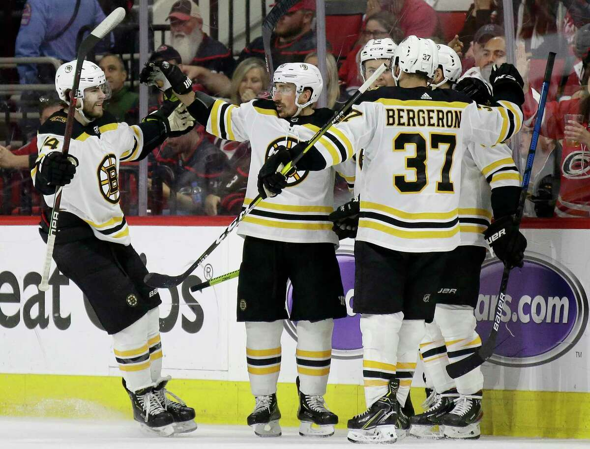 Boston Bruins' Jake DeBrusk, left, celebrates with Brad Marchand, Patrice Bergeron (37) and teammates following Marchand's goal against the Carolina Hurricanes during the second period in Game 3 of the NHL hockey Stanley Cup Eastern Conference final series in Raleigh, N.C., Tuesday, May 14, 2019. (AP Photo/Gerry Broome)