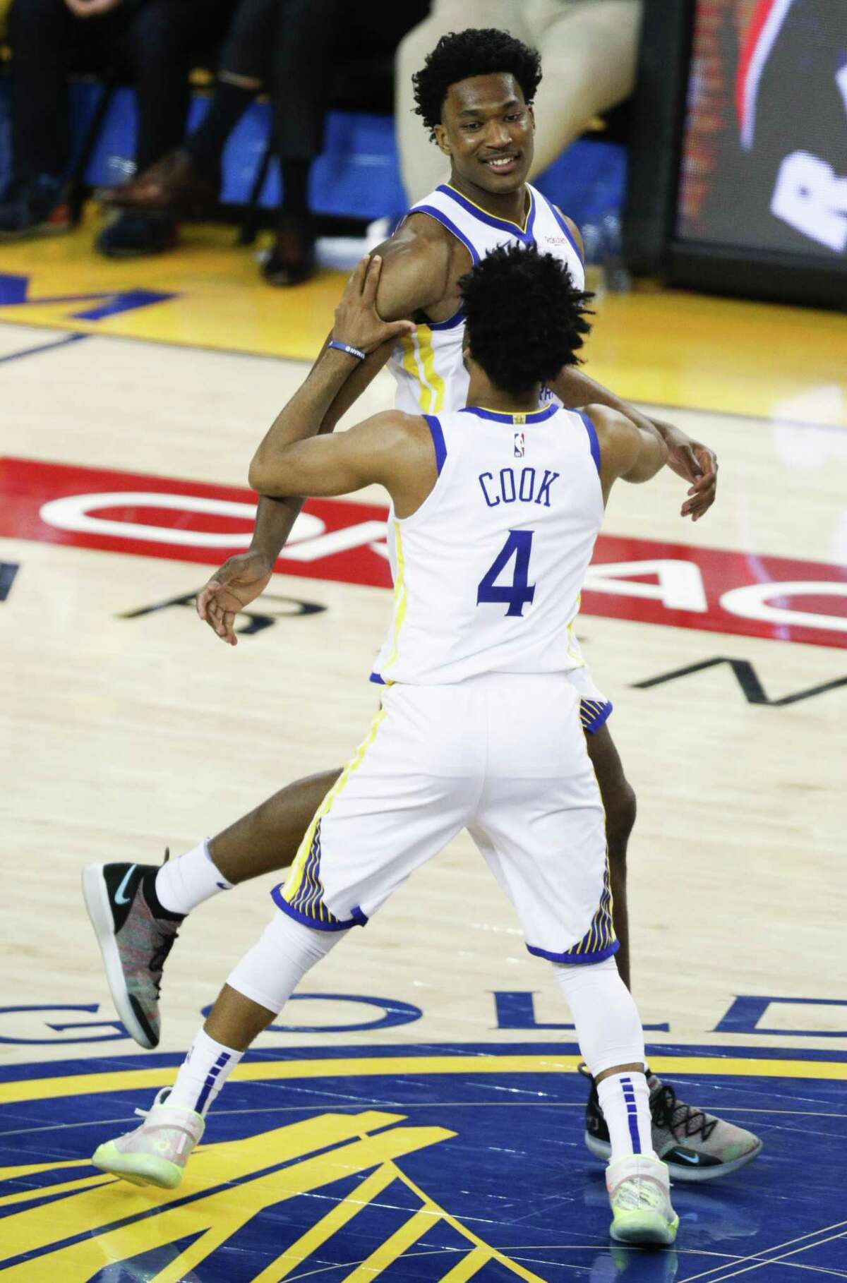 Golden State Warriors Quinn Cook and Damian Jones react to Jones' score in the fourth quarter during game 1 of the Western Conference Finals between the Golden State Warriors and the Portland Trail Blazers at Oracle Arena on Tuesday, May 14, 2019 in Oakland, Calif.