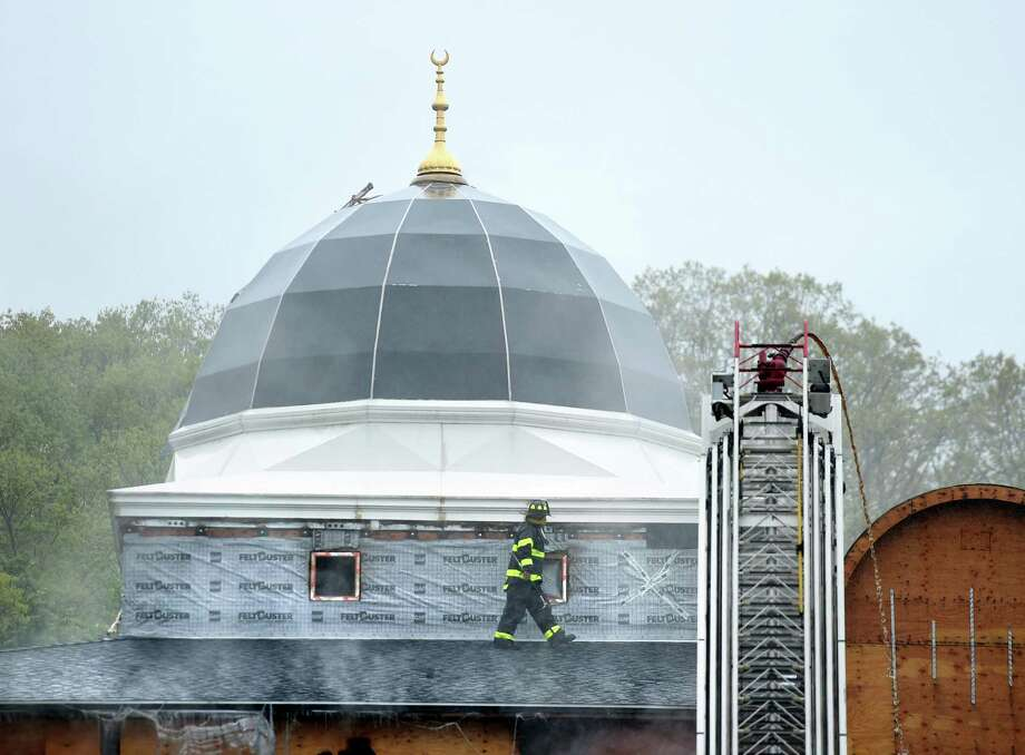 A New Haven firefighter walks across the roof of the Diyanet Mosque of New Haven on Middletown Avenue while responding to a fire on May 12, 2019. Photo: Arnold Gold / Hearst Connecticut Media / New Haven Register