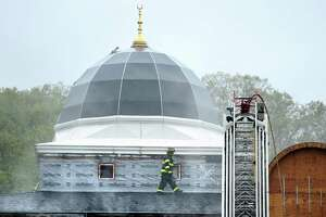 A New Haven firefighter walks across the roof of the Diyanet Mosque of New Haven on Middletown Avenue while responding to a fire on May 12, 2019.