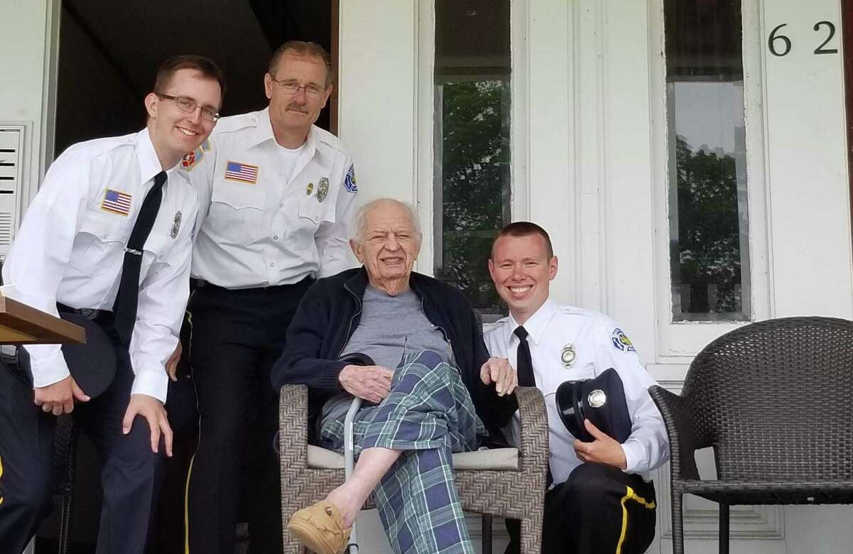 Native son Harry Cohen, who died April 27, is shown alongside local emergency service volunteers enjoying the 2018 Memorial Day parade from the porch of his Bridge Street home and office.