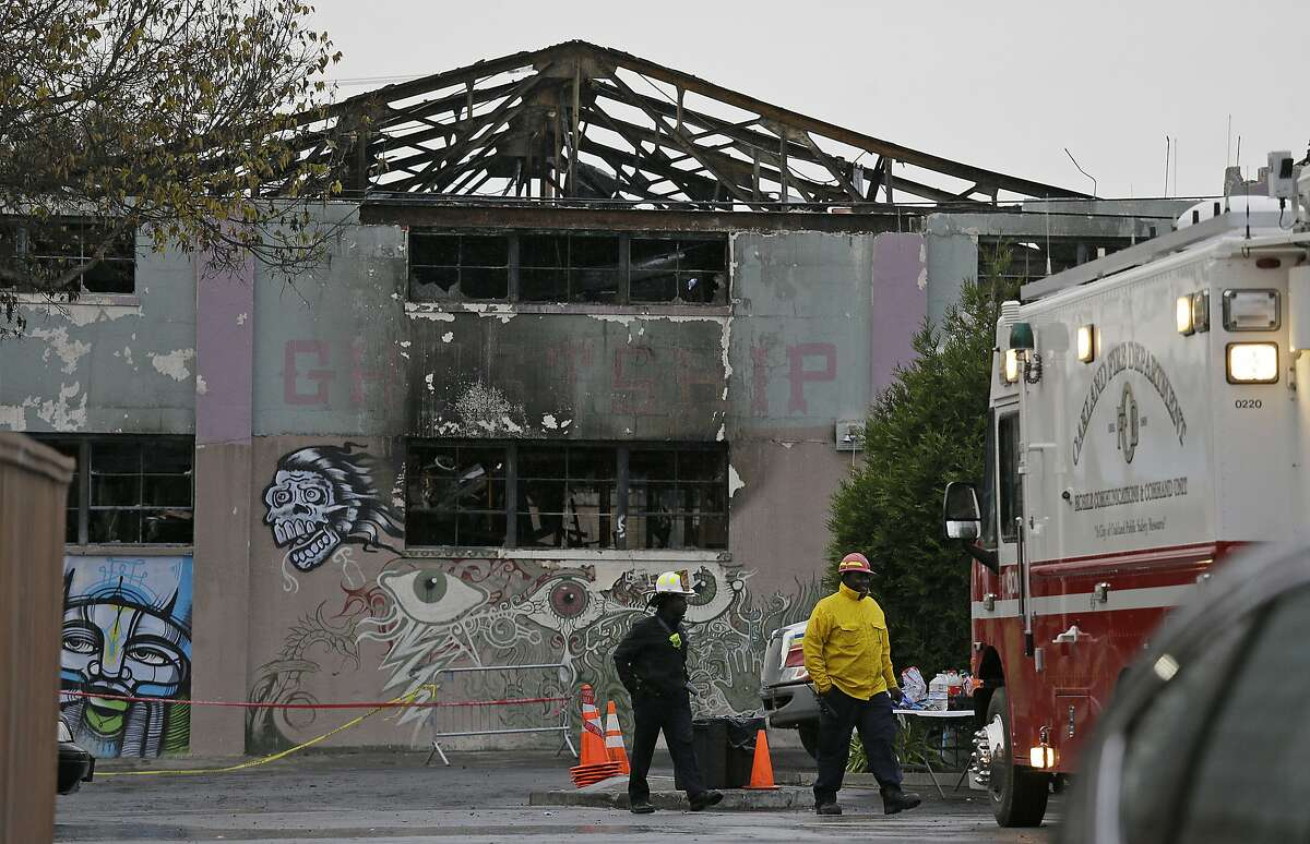 FILE - In this Dec. 7, 2016, file photo, Oakland fire officials walk past the remains of the Ghost Ship warehouse damaged from a deadly fire in Oakland, Calif. More than two years after 36 people died in the fire, Derick Almena and Max Harris, the two men who face charges of involuntary manslaughter, will stand trial on charges that they allegedly illegally converted the industrial building into an unlicensed entertainment venue and artist live-work space. (AP Photo/Eric Risberg, File)