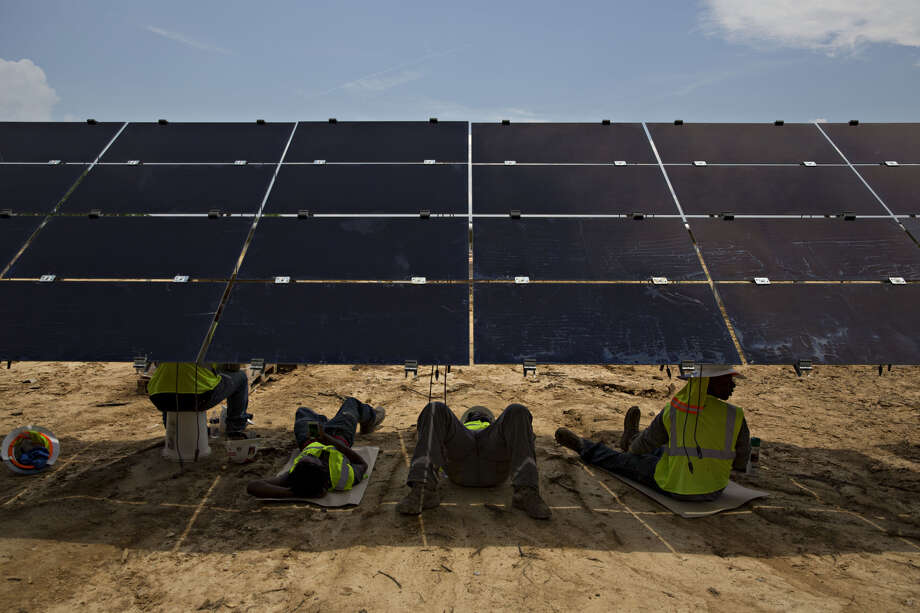 Workers take a break in the shade of a solar panel during construction of a Silicon Ranch Corp. solar generating facility in Milligan, Tennessee. Photo: Bloomberg Photo By Daniel Acker / Bloomberg